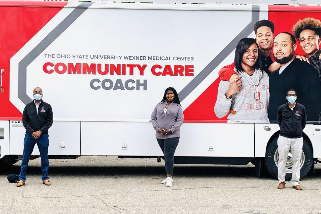 Drs. Darrell Gray, Timiya Nolan, and Joshua Joseph stand in front of the Community Care Coach.