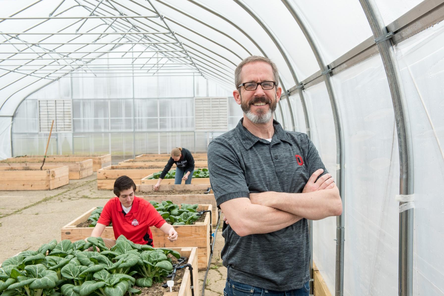 Professor Kip Curtis stands at the Mansfield Microfarm